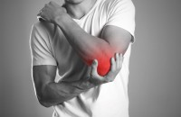 a man is holding a painful elbow shown in red